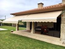 Toldo de sol modelo brazo articulado instalado en domicilio particular, estructura en aluminio blanco con tejido acrílico a juego.